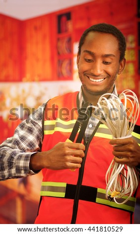 Young electrical worker wearing safety vest, holding cables and cable pliars, smiling with great positive attitude - stock photo