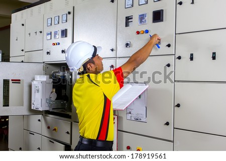 young electrician at work on distribution board - stock photo