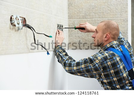 Young electrician at work with wall outlet and screwdriver installing sockets - stock photo