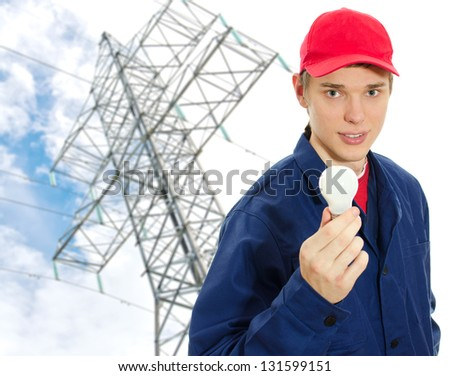 Young electrician in uniform with bulb on transmission tower background - stock photo