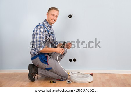 Young Electrician Stripping Wire With Plier In House - stock photo
