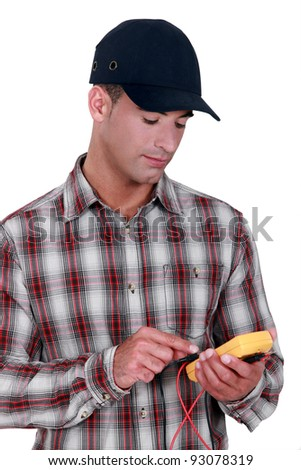 young electrician wearing cap using tester - stock photo