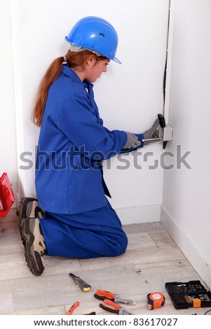 Young electrician working on power outlet - stock photo