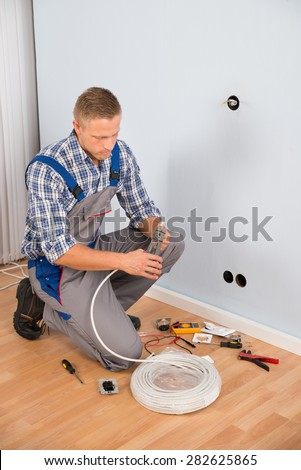 Young Electrician Working With Wire With Plier In House - stock photo
