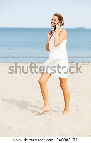 Young elegant beautiful woman talking on the phone on the beach. - stock photo