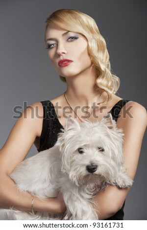 young elegant blond woman wearing black dress with an old fashion hairtyle and necklace jewellery, she looks in to the lens with actractive eyes and takes the dog in her arms