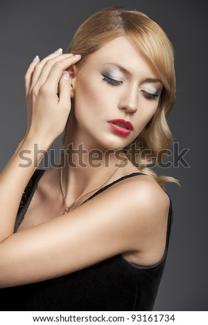 young elegant blond woman wearing black dress with an old fashion hairtyle and necklace jewellery, she looks down at the left and touches her hair with right hand - stock photo