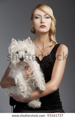 young elegant blond woman wearing black dress with an old fashion hairtyle and necklace jewellery, she is in front of the camera, takes a dog in her arms and looks in to the lens