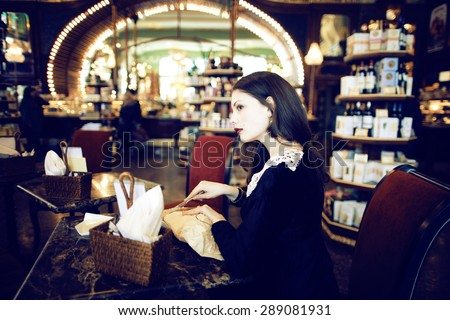 young elegant brunette woman in cafe drinking coffee, luxury interior - stock photo