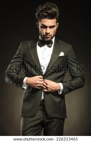 Young elegant business man looking at the camera while arranging his tuxedo. - stock photo