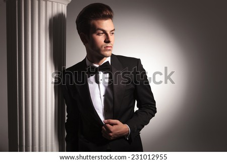 Young elegant business man looking away from the camera while leaning on a white column, fixing his jacket.