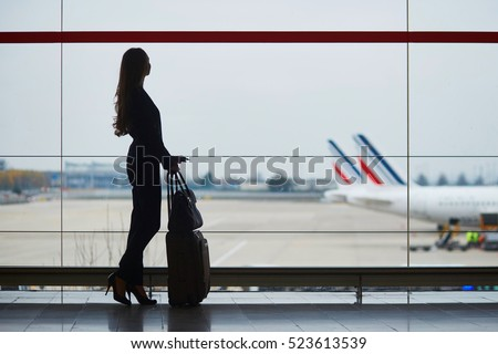 Young elegant business woman with hand luggage in international airport, looking through the window at planes. Cabin crew member with suitcase.