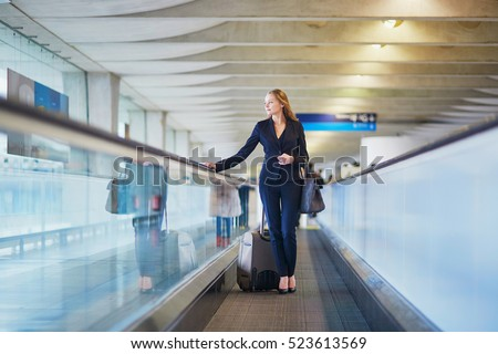 Young elegant business woman with hand luggage on travelator on international airport terminal. Cabin crew member with suitcase.