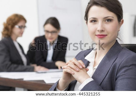 Young elegant businesswoman, in the background blurred image of two women discussing - stock photo