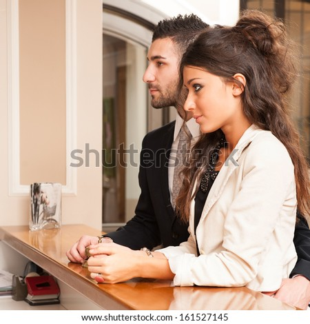 Young elegant couple at hotel reception. - stock photo