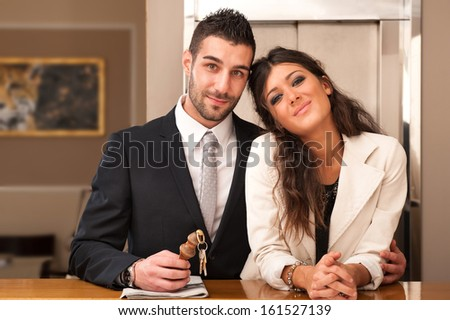 Young elegant couple at hotel reception with key room. - stock photo