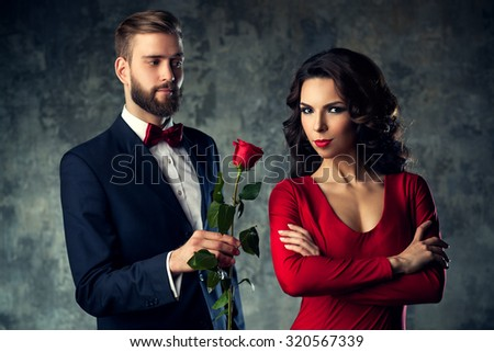 Young elegant couple in evening dress portrait. Man gives rose to woman. Focus on woman. - stock photo