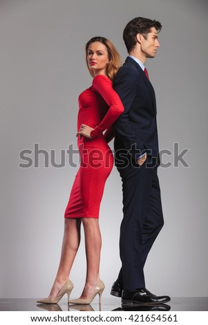 young elegant couple standing back to back in studio, woman in red dress, man in suit  - stock photo
