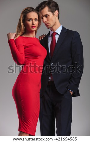 young elegant couple standing embraced, man in suit and tie, woman in red dress