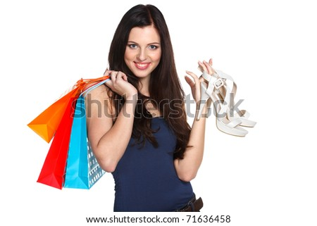 Young elegant female holding paper-bags with purchases and white high heel platform sandals isolated on white - stock photo