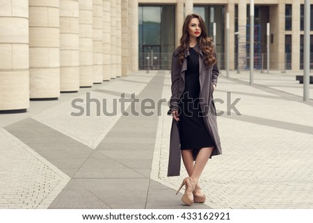 Young elegant girl posing at city street. Pretty beautiful business woman in elegant black dress and gray coat against city background. Full length horizontal portrait. - stock photo