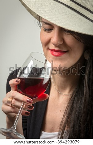 Young elegant girl with red lips and attractive hat drinking red wine with style feeling elegant and sexy. - stock photo