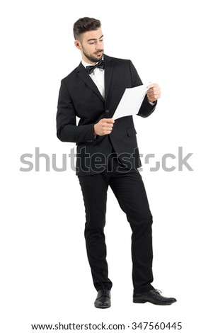 Young elegant groom holding and reading paper documents.  Full body length portrait isolated over white studio background.