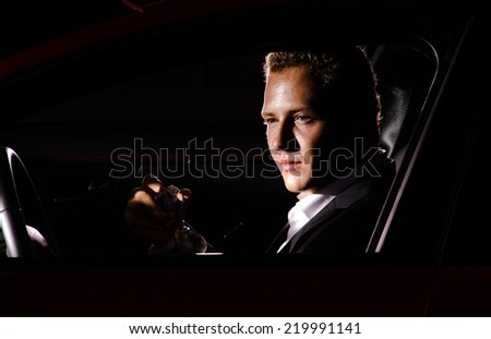 Young elegant guy sitting in luxury  modern red car