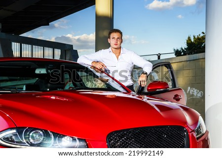Young elegant guy sitting in luxury  modern red car - stock photo