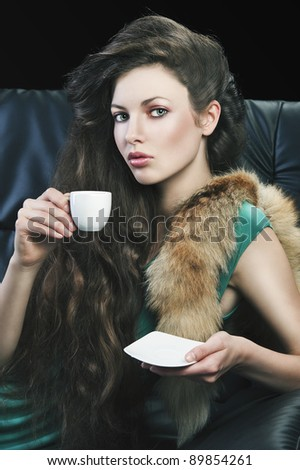 young elegant lady laying down on sofa keeping and drinking from a little cup of coffee. wearing green dress. She looks in to the lens, with right hand takes the cup and has saucer in left hand. - stock photo