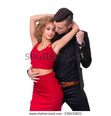 Young elegant loving couple portrait. Woman in red dress and man in black suit, isolated on white studio shot