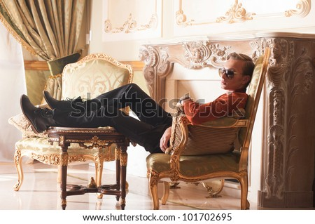 Young elegant man in royal interior sitting on armchair. - stock photo