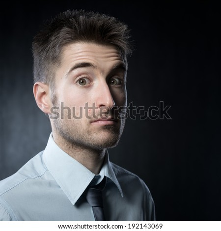 Young elegant man looking at camera expressing surprise.
