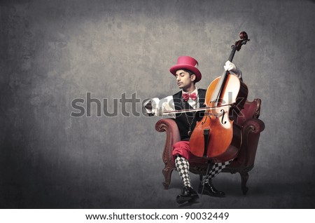 Young elegant man playing the cello - stock photo