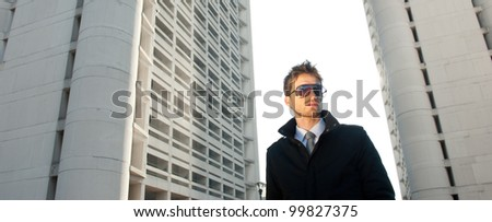 Young elegant man portrait with building background.