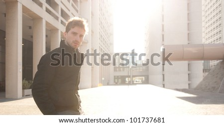 Young elegant man portrait with building background. Back light.