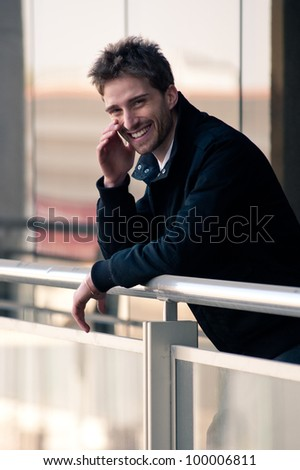 Young elegant man smiling with building background. - stock photo