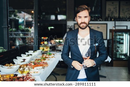 Young elegant man standing in the restaurant, holding a glass of wine. Man's style - stock photo