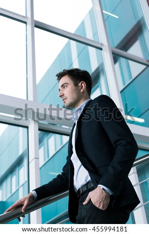 Young elegant man with his hand in his pocket, going down the stairs in a modern office building
