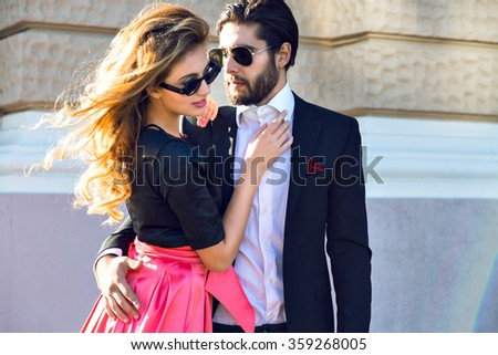 Young elegant sexy couple hugs on the street, wearing suit and glamour evening dress, enjoy their honeymoon vacation in Europe, luxury style, love, stylish lovers. - stock photo