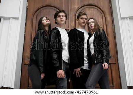 Young elegant trendy friends outdoors, wearing black and white clothing, retouched shot. - stock photo