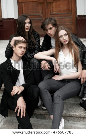 Young elegant trendy friends outdoors, wearing black and white clothing, retouched shot