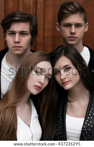 Young elegant trendy friends outdoors, wearing black and white clothing, retouched shot. Close up - stock photo
