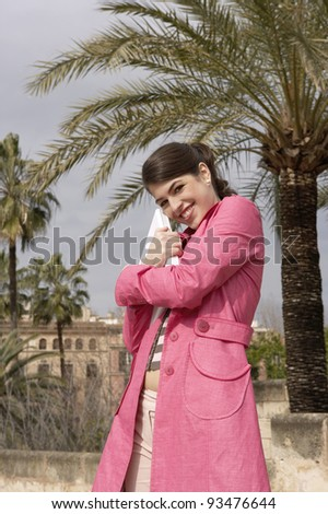 Young elegant woman hugging a laptop computer outdoors. - stock photo