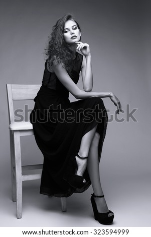 Young elegant woman in black long dress, shoes. Sitting and posing in studio. Curly hair, bright makeup. High fashion shot. Black and white