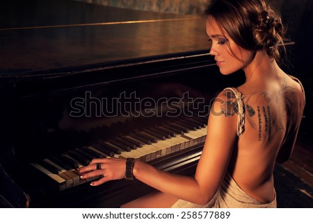 Young elegant woman in dress playing piano in retro style interior. - stock photo
