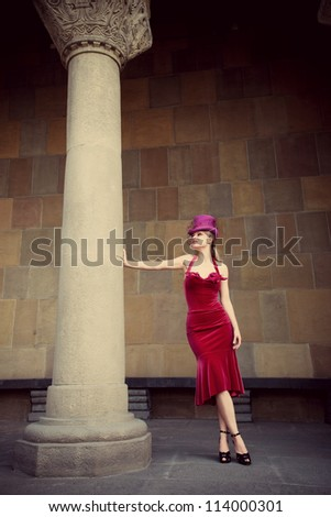 young elegant woman in red dress and cylinder  leaning against column, full body shot - stock photo