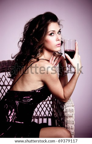 young elegant woman sit in armchair holding a glass of red wine, studio shot - stock photo