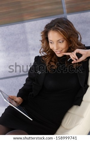 Young elegant woman using tablet computer, smiling.