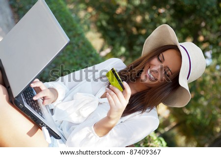 Young elegant woman wearing straw hat and white dress holding credit card with laptop sitting on bench at park and looking away. She is shopping or making payments carefree online - stock photo